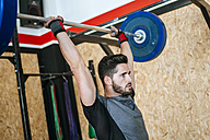 Man lifting barbell in gym - KIJF00923