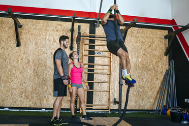 Athletes climbing a rope in gym - KIJF00926