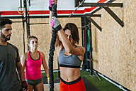 Athletes watching woman climbing a rope in gym - KIJF00929