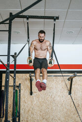 Man doing exercises on rings in gym - KIJF00938