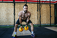 Man lifting kettlebells in gym - KIJF00944