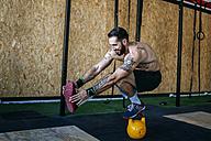Man keeping balance on a kettlebell in gym - KIJF00953