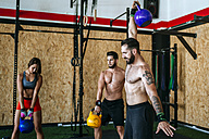 Group of athletes lifting kettlebells in gym - KIJF00956