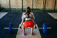 Back view of woman preapring to lift barbell in gym - KIJF00959