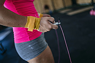 Close-up of woman holding skipping rope in gym - KIJF00962
