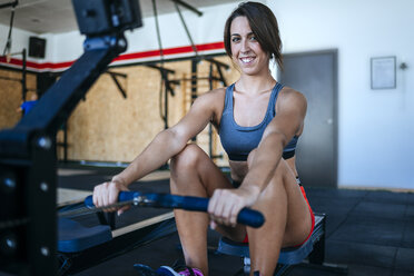 Smiling woman exercising with a rowing machine in gym - KIJF00968