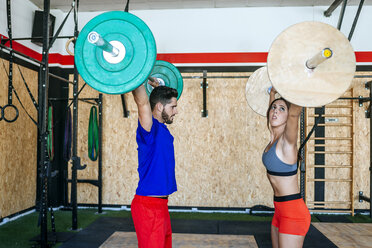 Man and woman lifting barbells in gym - KIJF00980