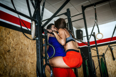 Couple kissing while exercising in gym - KIJF00983