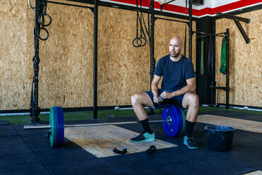 Man resting on barbell in gym - KIJF00986