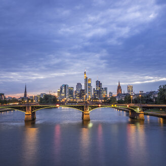 Germany, Frankfurt, view to financial district at blue hour with Ignatz-Bubis-Bridge in the foreground - KRPF02062