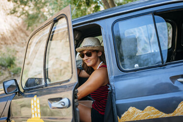 Morocco, Ouarzazate, portrait of smiling woman getting on her car - KIJF01003