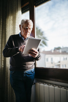 Senior man with tablet standing in front of window at home - JRFF01061