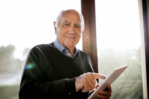 Portrait of smiling senior man with tablet standing in front of window - JRFF01064