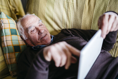 Senior man lying on couch using tablet - JRFF01067