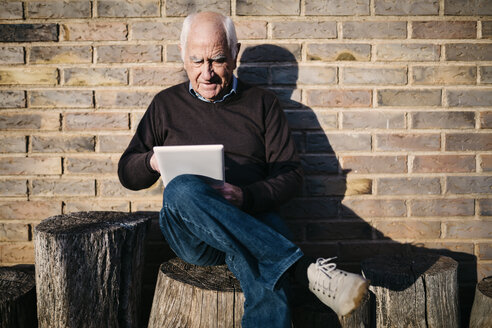 Senior man sitting on tree stump using tablet - JRFF01070