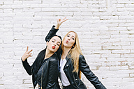 Two young women pouting mouth and showing victory sign in front of white brick wall - GEMF01284