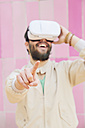 Smiling man wearing Virtual Reality Glasses in front of the pink wall - RTBF00535