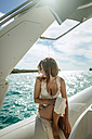 Woman sitting on a motor boat - KIJF01026