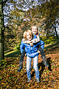 Portrait of boy giving his sister a piggy back ride in autumn - SARF03076