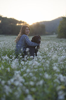 Young woman and her dog in field of flowers at twilight - SKCF00231