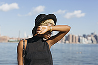 USA, New York City, Brooklyn, young woman at East River wearing a hat - GIOF01645