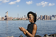 USA, New York City, Brooklyn, smiling young woman at East River with Manhattan skyline in background - GIOF01648