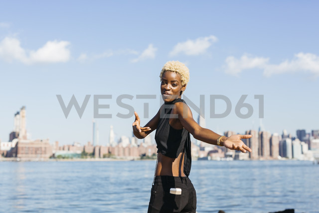 USA, New York City, Brooklyn, smiling young woman at East River - GIOF01651