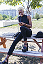 Smiling young woman sitting on wooden table looking on cell phone - GIOF01654
