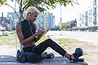 Smiling young woman with cell phone and earbuds - GIOF01663