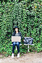 Young woman using laptop outdoors - GEMF01288
