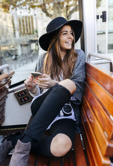Happy woman with cell phone on a tour bus - MGOF02625