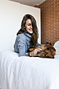 Happy young woman lying in bed playing with her dog - VABF00857