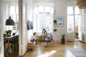 Woman at home sitting on chair talking on cell phone - FKF02079