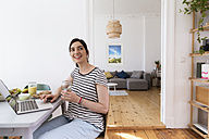 Smiling woman at home sitting at table using laptop - FKF02085