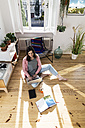 Woman at home sitting on floor using laptop - FKF02094
