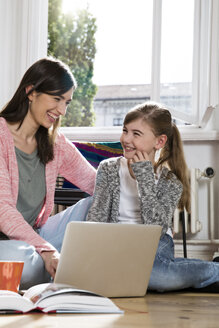 Happy mother and daughter at home sitting on floor using laptop - FKF02097