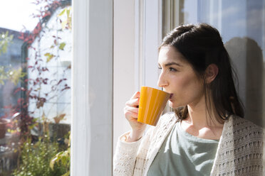 Woman drinking coffee at the window - FKF02115