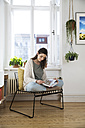 Woman at home sitting on chair reading book - FKF02121