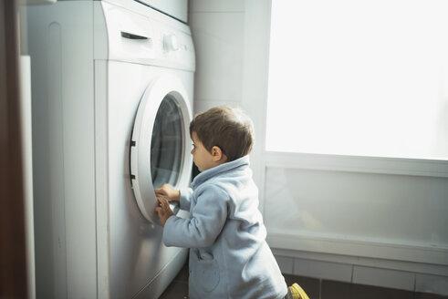 Baby boy watching washing machine at home - JASF01363