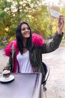 Young woman taking a selfie in a park in autumn - MGOF02657