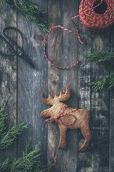 Elk-shaped Christmas cookie on dark wood - RTBF00550