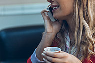 Smiling woman with takeaway coffee talking on cell phone, close-up - ZEDF00445