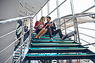 Two business people sitting on stairs of using cell phone - ZEDF00451