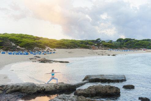 Pregnant woman practising yoga at the sea - DIGF01454