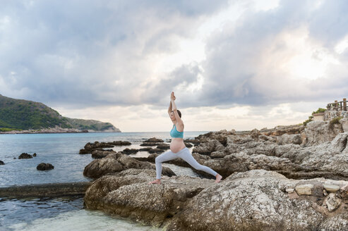Pregnant woman practising yoga at the sea - DIGF01457