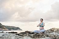 Pregnant woman practising yoga at the sea - DIGF01466