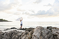 Happy pregnant woman on the beach holding a cloth - DIGF01484