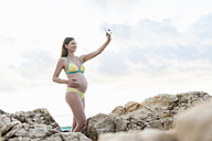 Pregnant woman between rocks at the sea taking a selfie - DIGF01490