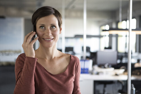 Smiling businesswoman in office on cell phone - RBF05247