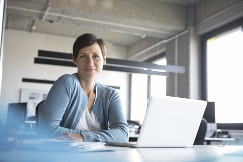 Portrait of smiling businesswoman in office with laptop - RBF05259